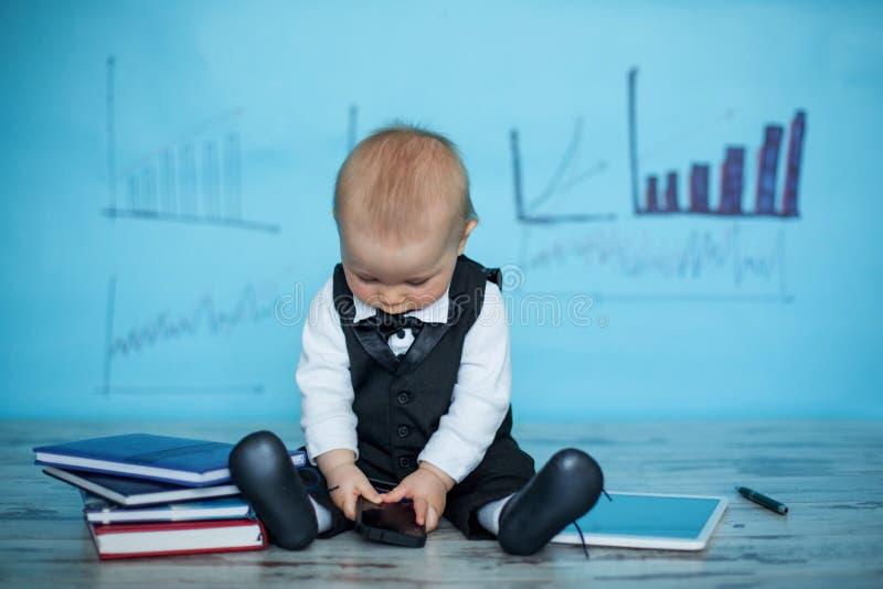 Niño pequeño lindo, vestido en el traje y el arco, hablando en el teléfono imagen de archivo libre de regalías