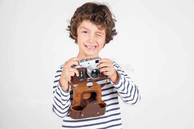 Niño pequeño lindo y divertido con la cámara vieja de la película sobre el backgr blanco imagen de archivo