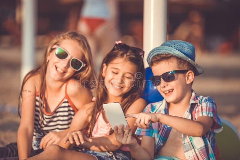 Niño pequeño lindo y muchachas que se sientan en la playa que juega con el teléfono elegante imagen de archivo