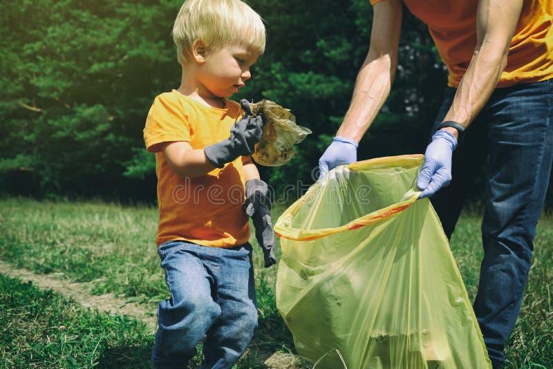 Niño pequeño lindo y su padre que recogen la basura en el parque Familia de los voluntarios que coge la litera en el bosque ambie imágenes de archivo libres de regalías