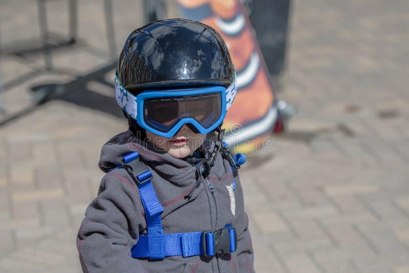 Niño pequeño listo para esquiar con todo el engranaje de la seguridad Casco y arnés fotografía de archivo