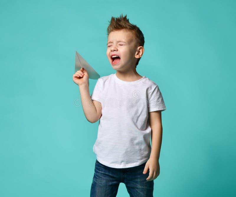 Niño pequeño listo para poner en marcha un avión de papel pero grito con los ojos cerrados Nuevo paso de progresión foto de archivo libre de regalías