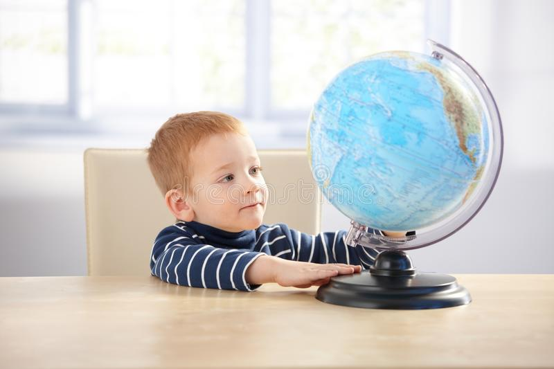 Niño pequeño pelirrojo dulce que estudia el globo imagen de archivo libre de regalías