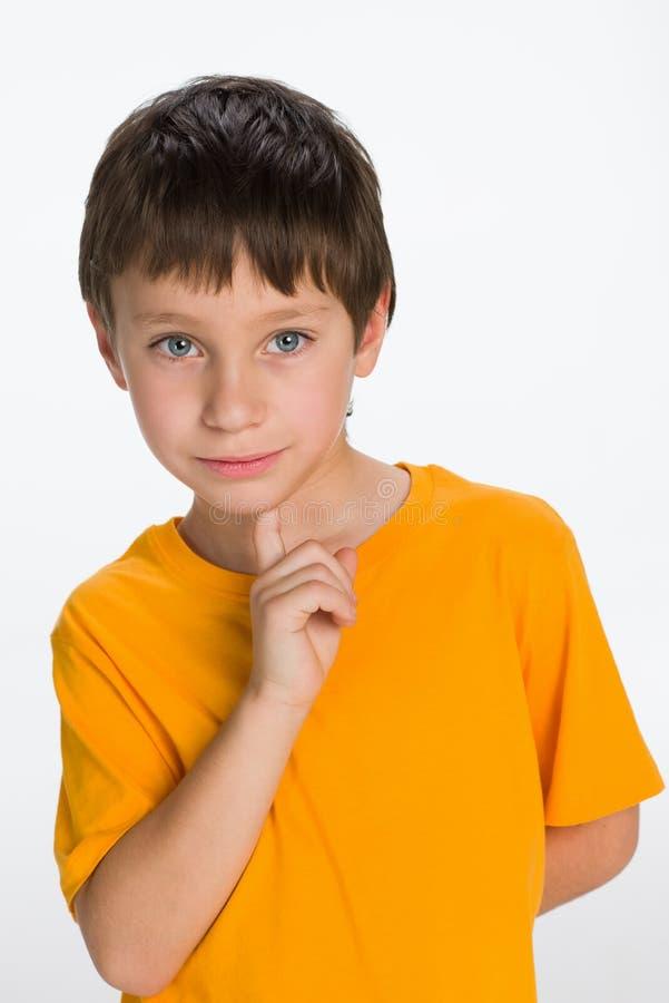 Niño pequeño pensativo en una camisa amarilla fotos de archivo