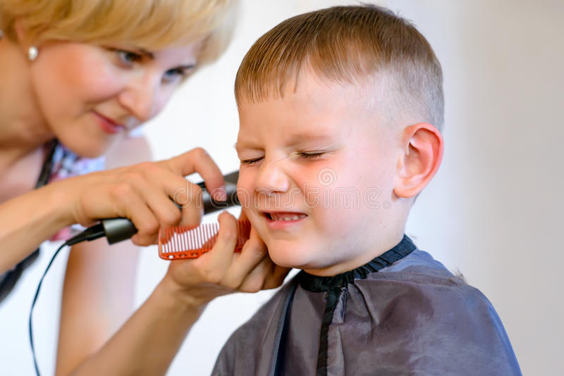 Niño pequeño poco impresionado con su corte de pelo imagen de archivo libre de regalías