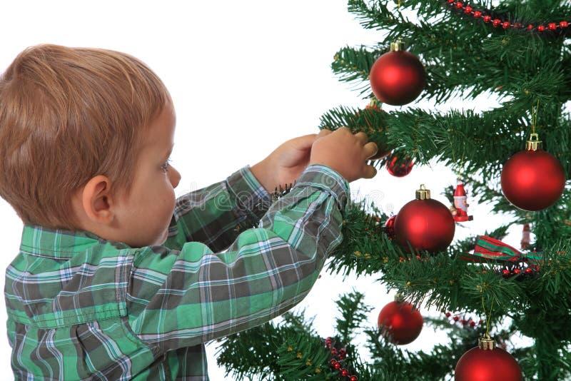 Niño pequeño que adorna el árbol de navidad fotografía de archivo