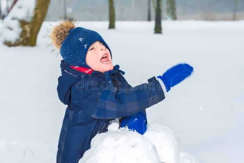 Niño pequeño que agita su mano en la nieve El niño está jugando imágenes de archivo libres de regalías