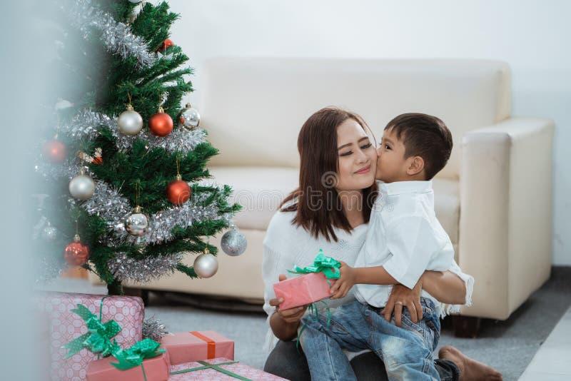 Niño pequeño que agradece a su mamá por el regalo foto de archivo