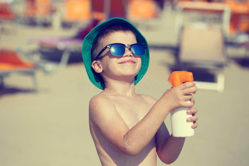 Niño pequeño que aplica el vintage del espray de la protección solar imagenes de archivo