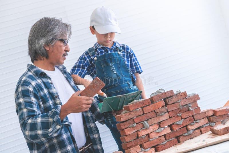 Niño pequeño que aprende cómo construir la pared de ladrillo de su abuelo de la construcción fotografía de archivo libre de regalías