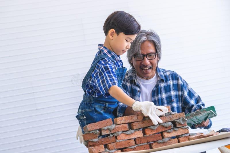 Niño pequeño que aprende cómo construir la pared de ladrillo de su abuelo de la construcción fotos de archivo
