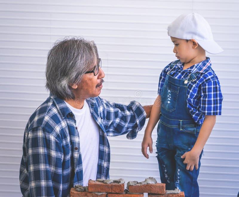 Niño pequeño que aprende cómo construir la pared de ladrillo de su abuelo de la construcción foto de archivo