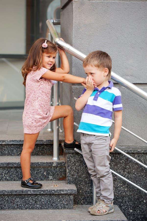 Niño pequeño que besa la mano de la niña. imágenes de archivo libres de regalías