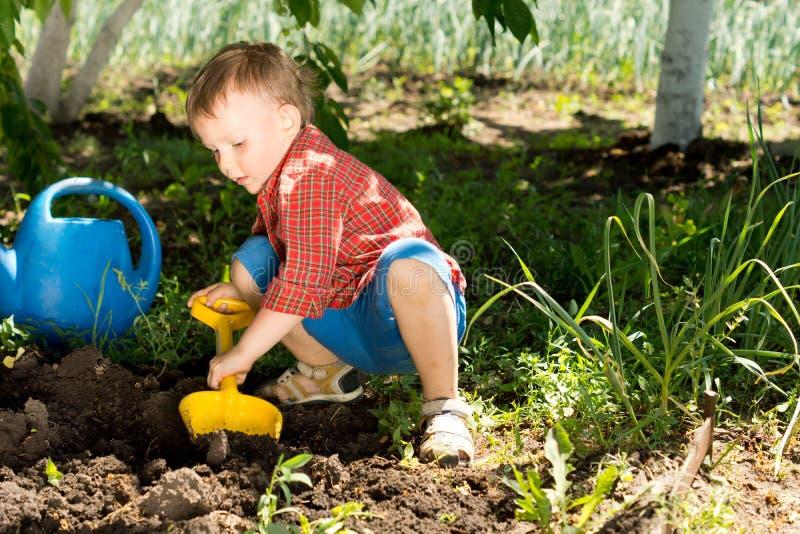 Niño pequeño que cava con una espada del juguete imagen de archivo libre de regalías