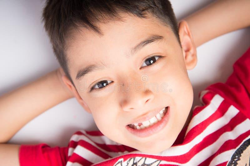 Niño pequeño que coloca en el cierre de la opinión superior del piso para arriba que sonríe imagenes de archivo