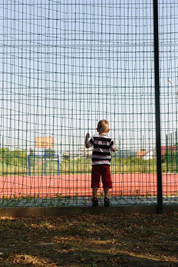 Niño pequeño que coloca la cerca cercana de la red imagen de archivo
