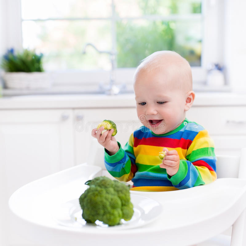 Niño pequeño que come el bróculi en la cocina blanca fotografía de archivo libre de regalías