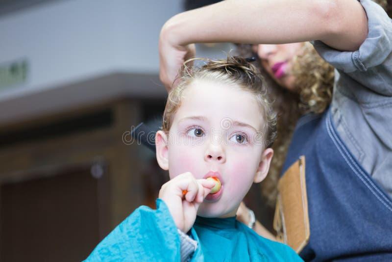 Niño pequeño que come el caramelo en silla de peluquero foto de archivo libre de regalías