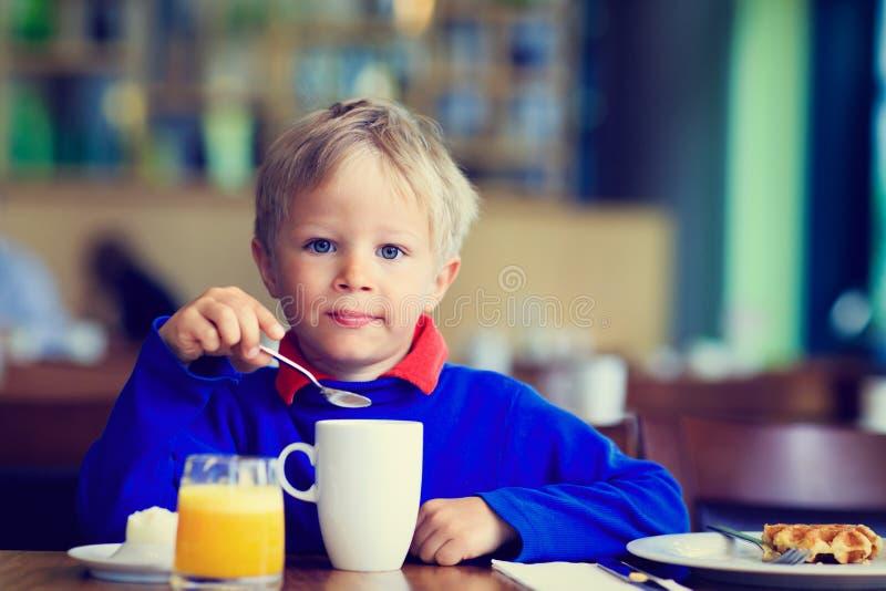 Niño pequeño que come el desayuno en café imagen de archivo libre de regalías