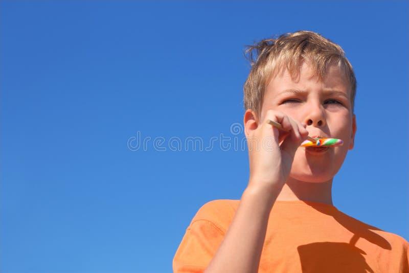 Niño pequeño que come el lollipop multicolor fotos de archivo libres de regalías