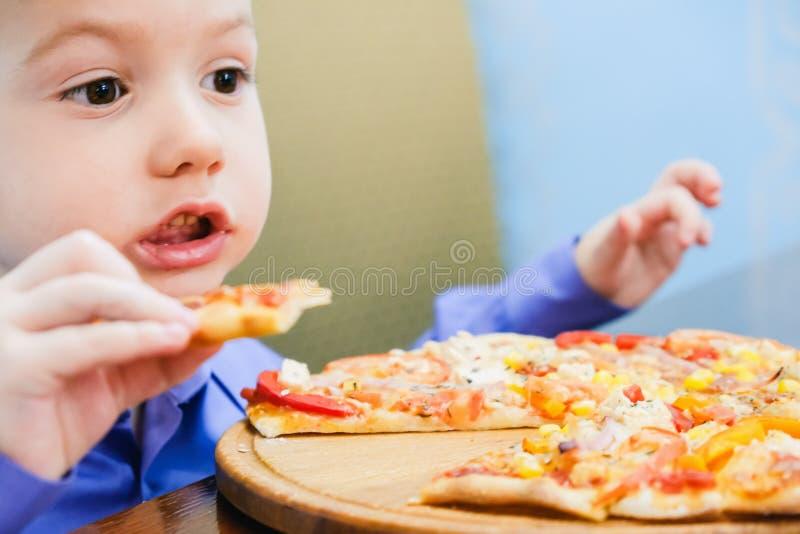 Niño pequeño que come la pizza en el café imagen de archivo