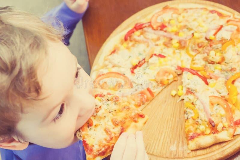 Niño pequeño que come la pizza en el café imagenes de archivo