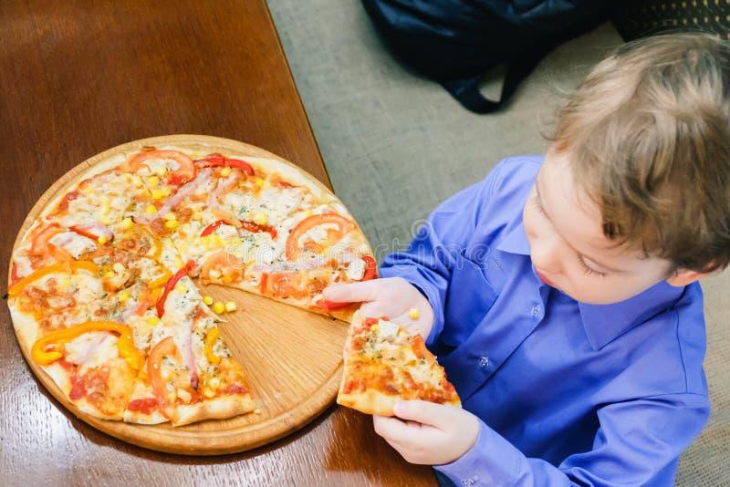 Niño pequeño que come la pizza en el café foto de archivo