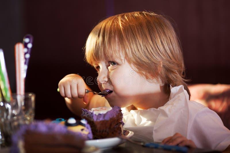 Niño pequeño que come la torta de chocolate fotos de archivo libres de regalías