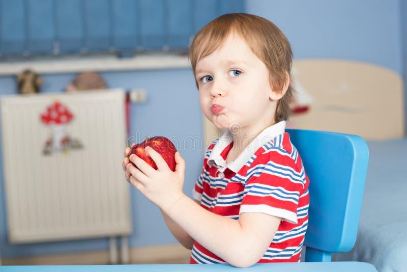 Niño pequeño que come una manzana fotos de archivo libres de regalías