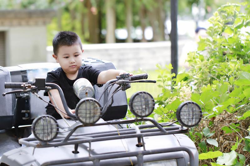 Niño pequeño que conduce el coche del juguete, juego joven del muchacho de la foto retra del vintage en coche del pedal imagen de archivo libre de regalías