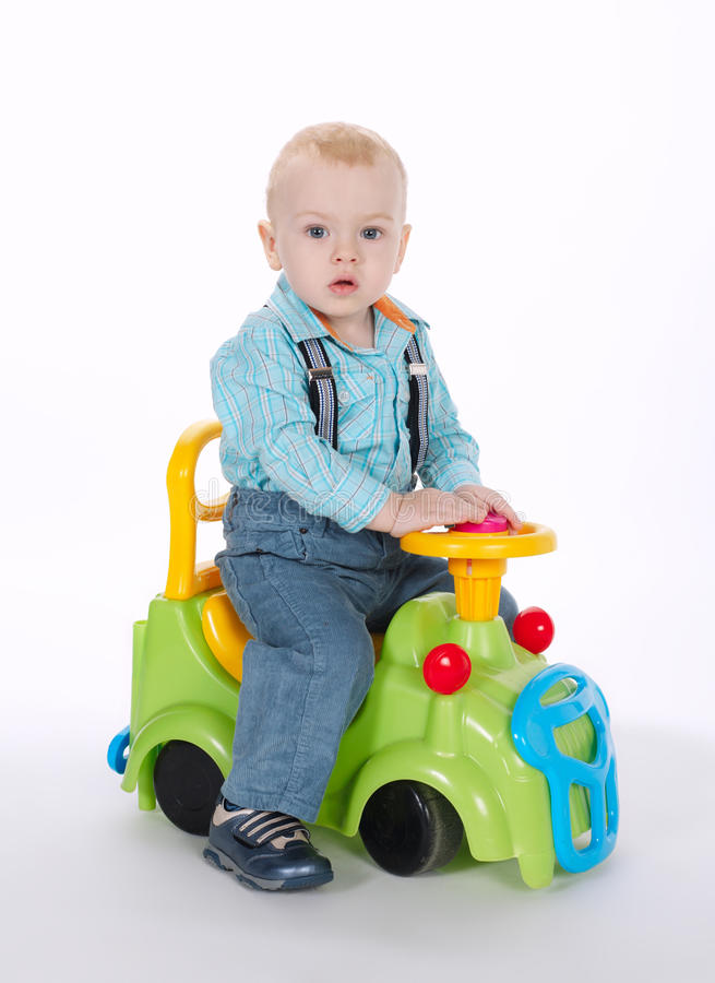 Niño pequeño que conduce en el coche del juguete fotos de archivo