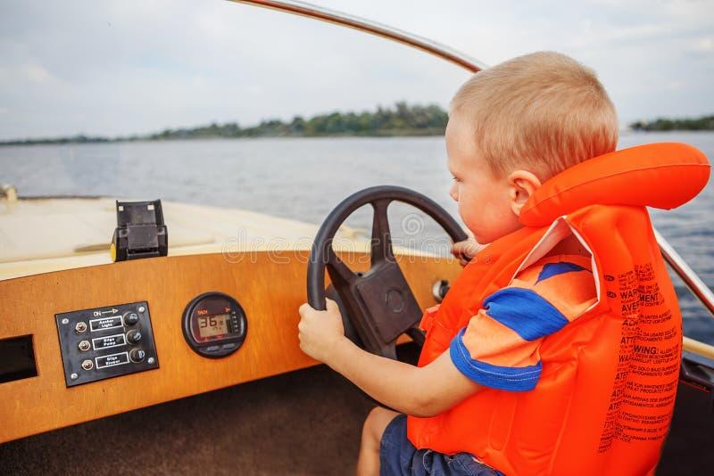 Niño pequeño que conduce un barco de motor que celebra firmemente la dirección whee fotografía de archivo libre de regalías