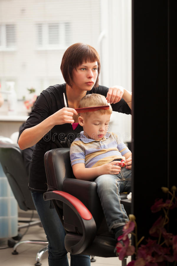 Niño pequeño que consigue un corte de pelo de peluquero imágenes de archivo libres de regalías