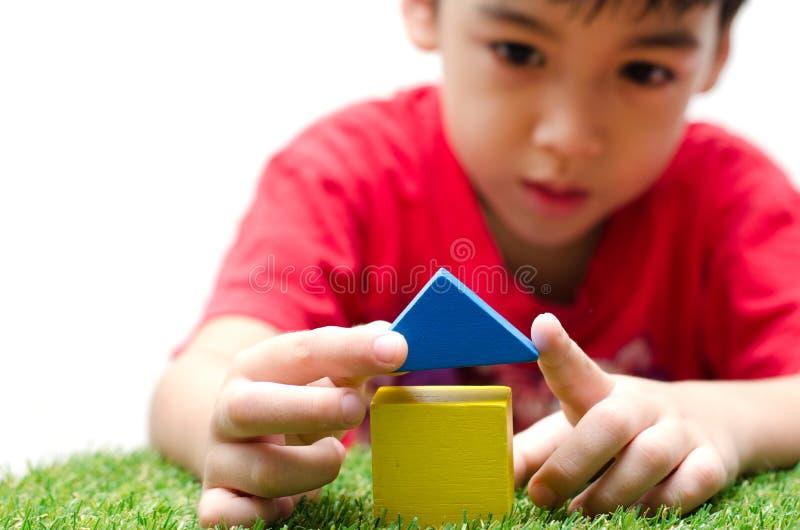 Niño pequeño que construye una pequeña casa con los bloques de madera coloridos foto de archivo libre de regalías