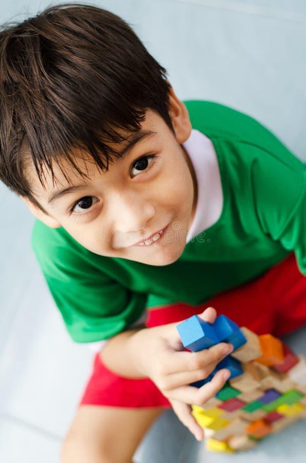Niño pequeño que construye una pequeña casa con los bloques de madera coloridos fotografía de archivo