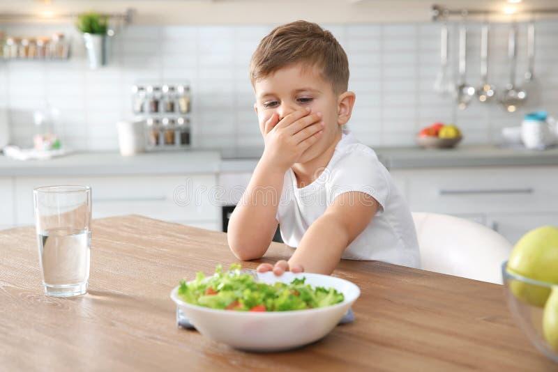 Niño pequeño que cubre su boca y que rechaza comer la ensalada vegetal en la tabla imagen de archivo libre de regalías