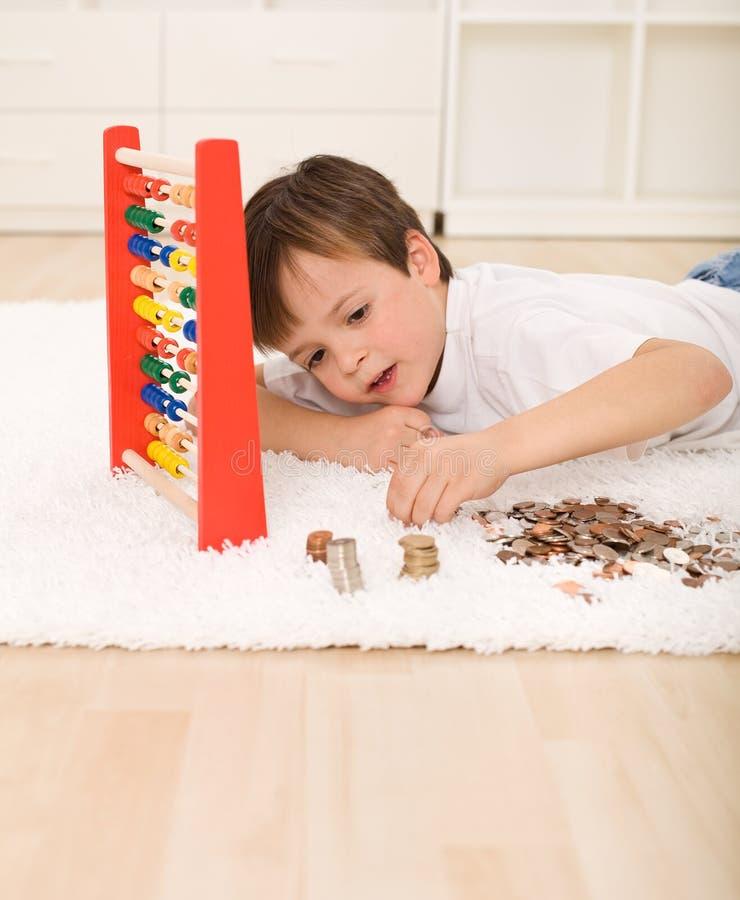Niño pequeño que cuenta sus ahorros imágenes de archivo libres de regalías