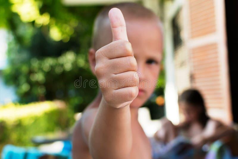 Niño pequeño que da los pulgares para arriba imagen de archivo libre de regalías