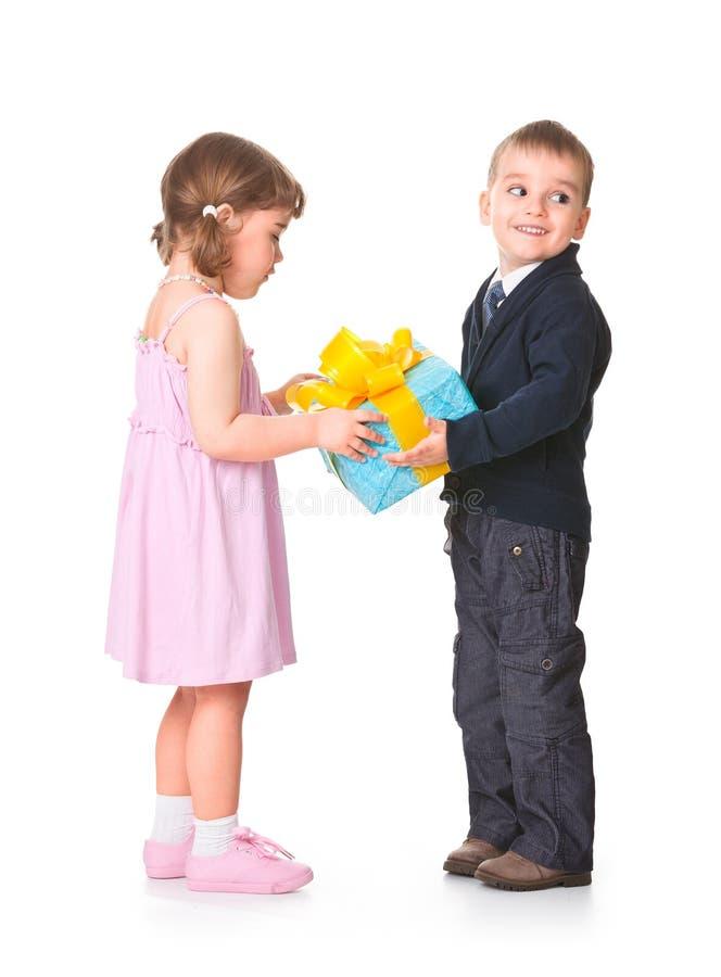 Niño pequeño que da un rectángulo de regalo a su novia imagenes de archivo