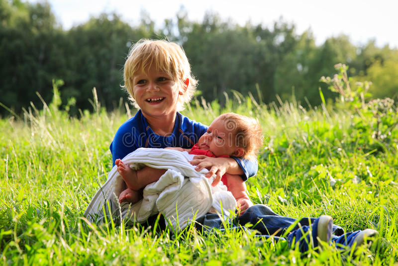 Niño pequeño que detiene a la hermana recién nacida en naturaleza del verano imagen de archivo
