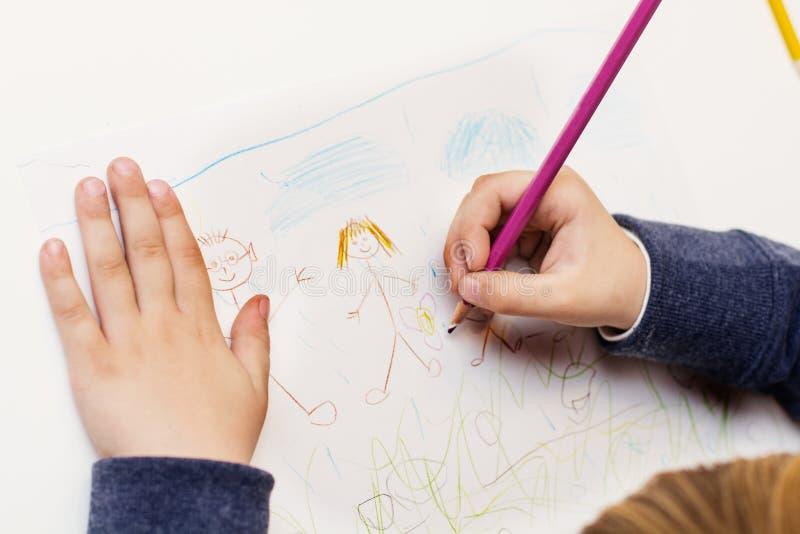 Niño pequeño que dibuja a la familia feliz imagenes de archivo
