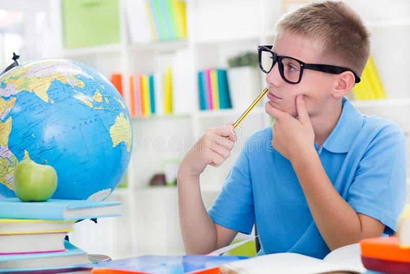 Niño pequeño que estudia sobre el mundo, y thinkig algo fotografía de archivo