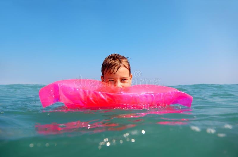 Niño pequeño que flota en el mar en matress fotos de archivo libres de regalías