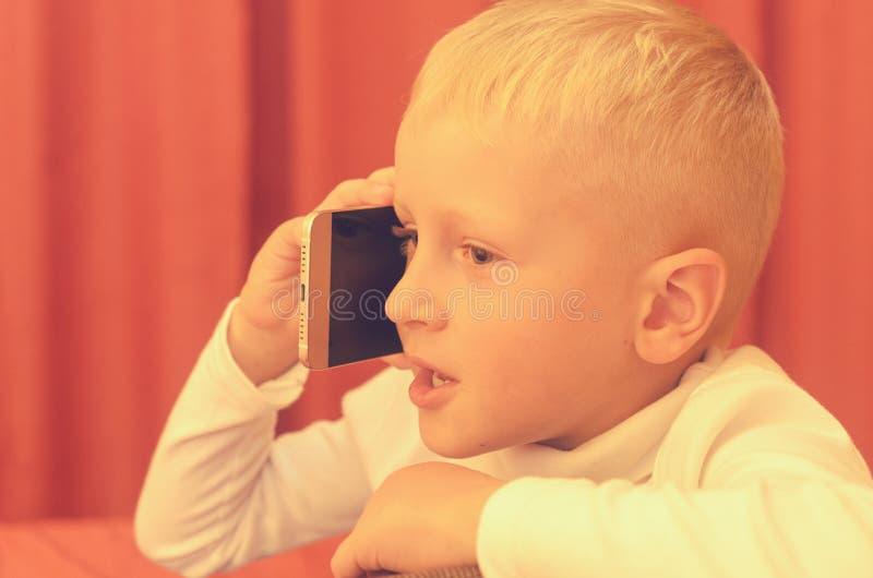 Niño pequeño que habla en el teléfono que expresa sus emociones foto de archivo
