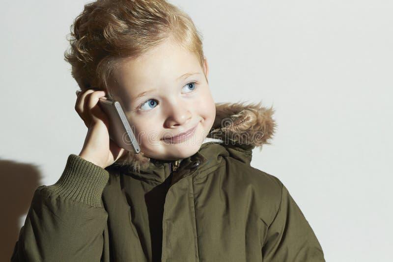 Niño pequeño que habla en el teléfono móvil niño moderno en abrigo de invierno Niños de la moda Niños foto de archivo