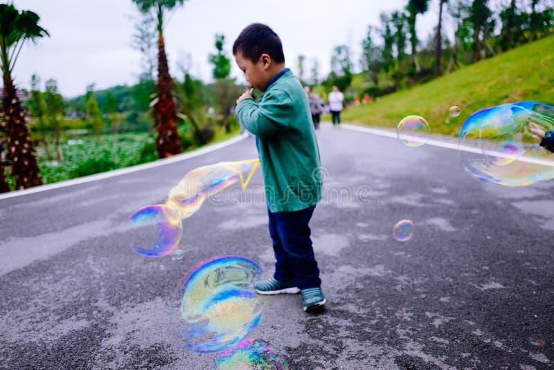 Niño pequeño que hace burbujas de jabón imagen de archivo