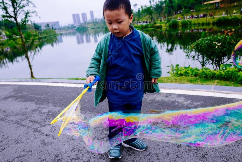 Niño pequeño que hace burbujas de jabón fotografía de archivo