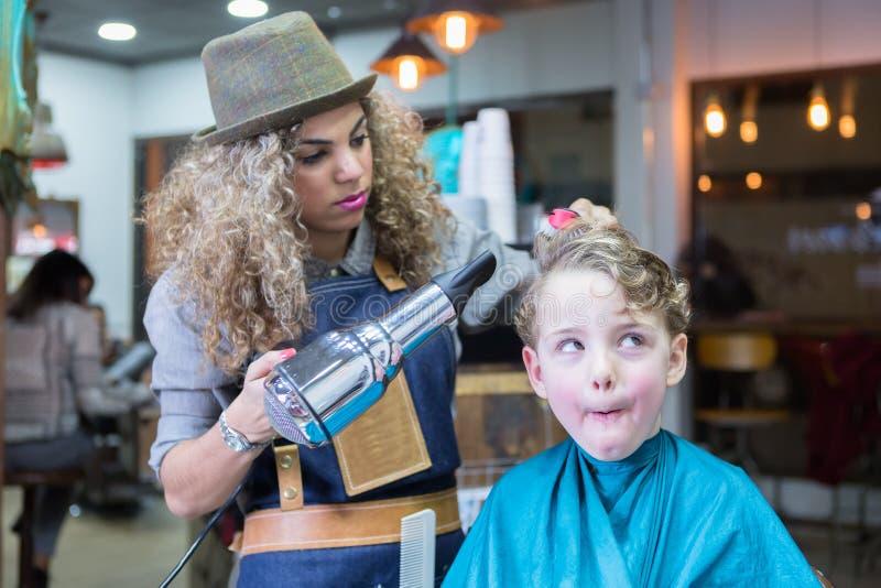 Niño pequeño que hace caras en silla de peluquero fotografía de archivo