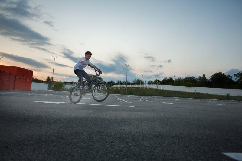 Niño pequeño que hace los trucos que saltan la bici que monta imagen de archivo libre de regalías