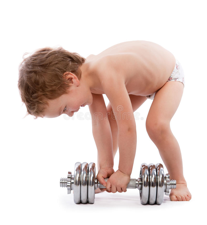 Niño pequeño que intenta levantar pesa de gimnasia pesada fotos de archivo